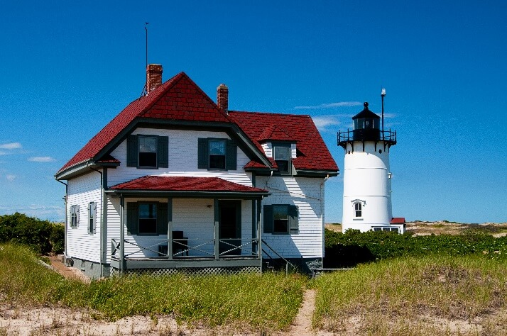 historic lodging in cape cod_old house with lighthouse in back