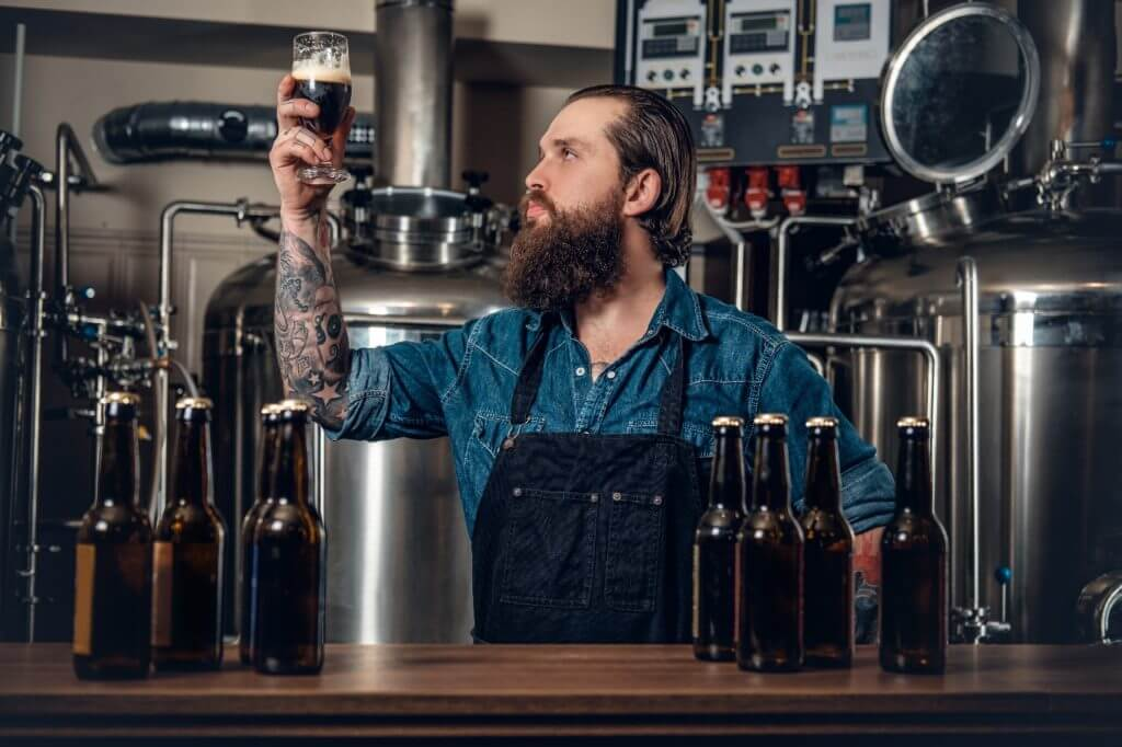 person holding up beer at cape cod brewery examining it_cape cod beer_cape cod craft beer_breweries in cape cod