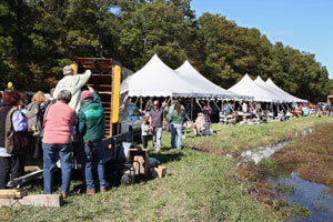 people gathered at event with tents at cape cod herring runs