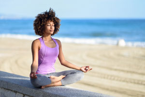 person meditating near beach_cape cod wellness_things to do on cape cod