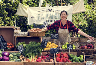 person with stand smiling at cape cod farmers markets_things to do on cape cod
