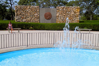 historical landmark in cape cod_person sitting on bench by fountain and wall