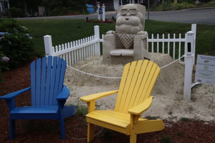 chairs in front of sand art at yarmouth sand sculpture trail