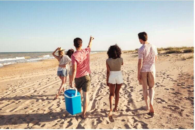group with cooler walking on beach_things to do on cape cod
