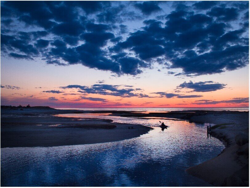 sunset and kayak on water in cape cod_best time to visit cape cod