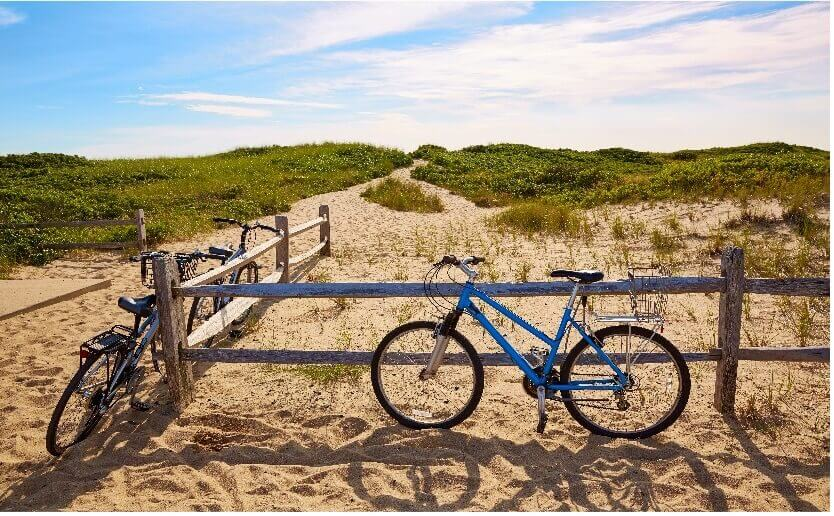 bicycles by fence on sand in cape cod_things to do on cape cod