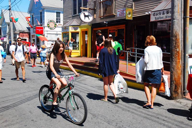 person biking on road near shops in cape cod_cape cod travel guide tips